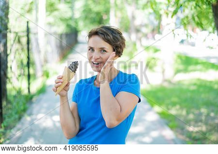 Happy Caucasian Girl In Blue Dress Eats Chocolate Ice Cream Cone Outdoors. Emotional Excited Short-h