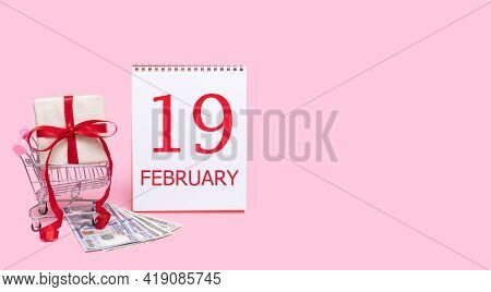19th Day Of February. A Gift Box In A Shopping Trolley, Dollars And A Calendar With The Date Of 19 F