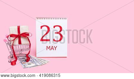 23rd Day Of May. A Gift Box In A Shopping Trolley, Dollars And A Calendar With The Date Of 23 May On