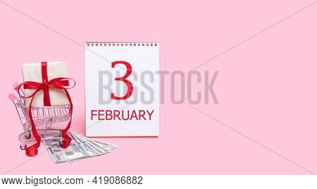 3rd Day Of February. A Gift Box In A Shopping Trolley, Dollars And A Calendar With The Date Of 3 Feb