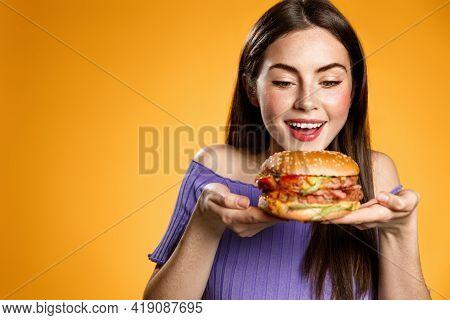 Happy Woman Looking At Tasty Hamburger. Girl Finally Receive Food Order, Grab Takeaway From Restaura
