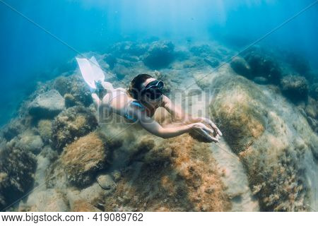 Freediver Woman Glides On Deep Sea. Free Diver With Fins Posing Underwater In Blue Ocean