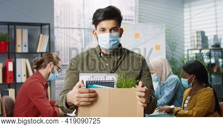 Portrait Of Young Handsome Hindu Man Employee In Medical Mask Standing In Cabinet Holding Carton Box
