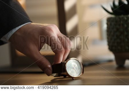 Man Putting Luxury Wrist Watch On Table, Closeup