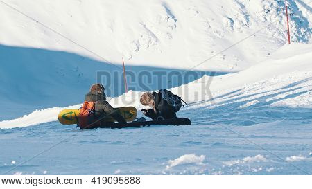 Kasprowy Wierch, Poland 28.01.2021 - Two Skiers Sitting On A Snow-covered Mountain - Skiers Taking A