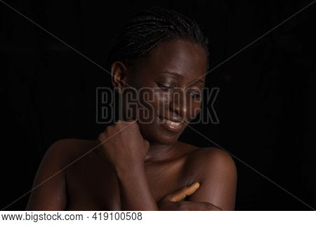 Portrait Of Smiling Woman With Beautiful Skin Posing Naked Torso And Hands On Breast Isolated Black