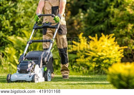 Caucasian Garden Worker In His 40s Cutting Grass Using Modern Electric Cordless Lawnmower In Large B