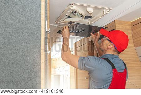 Caucasian Rv Appliances Technician In His 40s Repairing Air Condition Unit Inside Modern Travel Trai