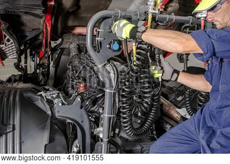 Caucasian Semi Truck Mechanic Performing Diesel Engine Maintenance With Scheduled Checkup. Transport