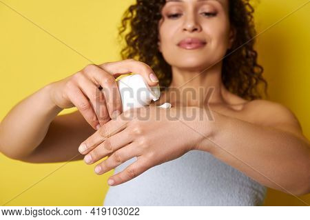 Close-up Of Female Hands Using Hand Cream To Rehydrate Skin, Isolated Over Yellow Background. Soft F