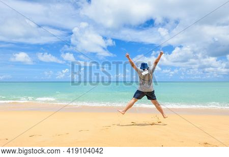 Excited Energetic Happy Tourist Man Hang Face Masks And Jumping At The Beach On Summer Vacations, Fu