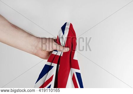 State Flag Of Great Britain In Hand On A White Background. A Man Holds The Flag Of The United Kingdo
