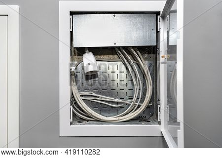 Open Multimedia Box With Antenna, Internet And Power Cables, Placed In The Gray Wall Of The Garage.