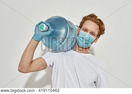 Cropped Photo Of A Young Deliveryman In White T-shirt With A Huge Bottle Which He Is Carrying On His