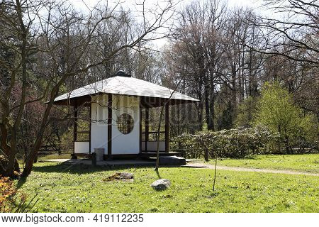 Traditional Gazebo In Japanese Garden, Oriental Culture. House Built In Retro Style Surrounded By Tr