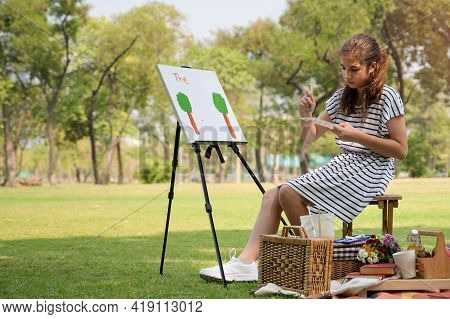 A Half-thai-european Girl  Is Sitting On The Wooden Bench And Painted On The Canvas Placed On A Draw