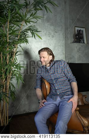 The Handsome Stylish Young Man Sits On An Expensive Leather Armchair Relaxed, Long Curly Hair, He Is