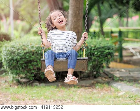 A Cute Asian Girl Was Playing On A Playground Swing And Having Fun