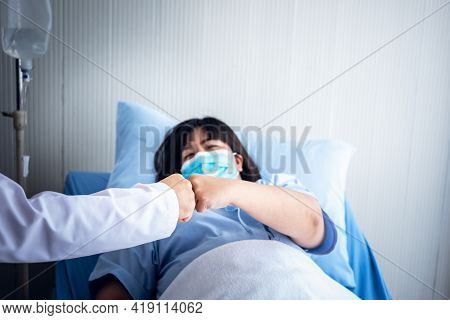 Doctor And Patient Which Wearing A Surgical Mask, Use Hands Fist Bump To Encouragement, Cooperation