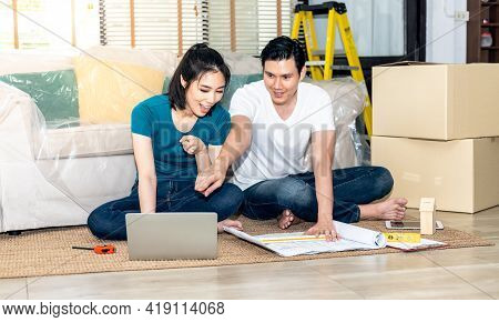 Asian Couple, Husband And Attractive Wife Looking At Computer Notebook And Discuss About Renovating