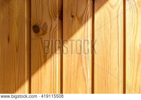 Fragment Of The Wall, Sheathed With Wooden Planks, Is Illuminated Diagonally By Sunlight. Vertical P