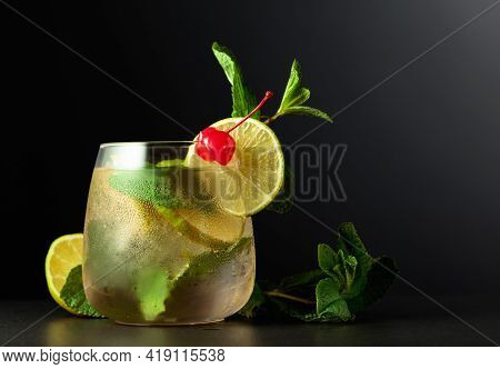 Cold Refreshing Drink With Lime Slices, Mint, And Cherry. Frozen Glass With A Mojito Garnished With