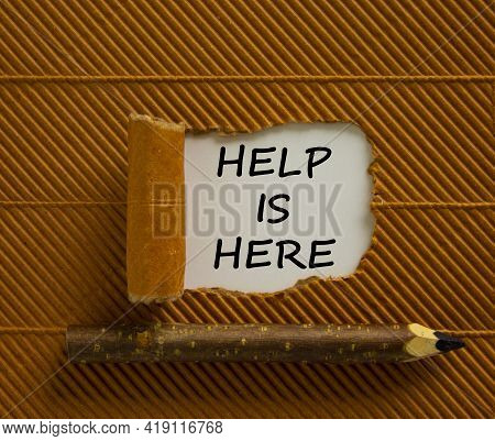 Support And Help Is Here Symbol. Words 'help Is Here' Appearing Behind Torn Brown Paper. Beautiful B