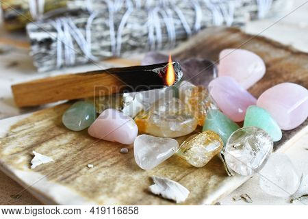 A Close Up Image Of Burning Wooden Incense With Small Polished Healing Crystals.
