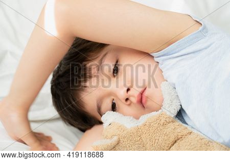 Kid 7 Year Old Lying On Bed, Sleepy Child Waking Up The Morning In His Bed Room With Morning Light,