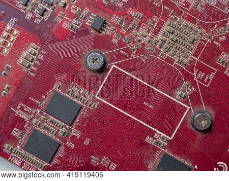Red Circuit Board With Chips And Capacitors. Electronic Board Close-up
