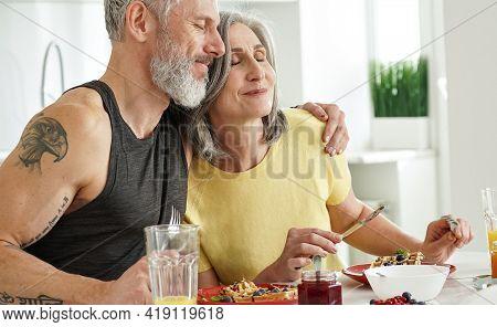 Happy Affectionate Mature Adult Husband Embracing Older Wife Enjoying Having Morning Breakfast Toget