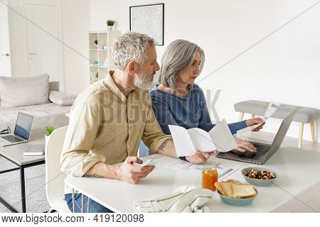 Middle Aged Couple Paying Financial Bills Online Using Computer At Home. Older Mature Husband And Wi