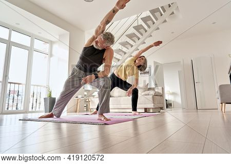 Fit Middle Aged 50s Family Couple Doing Fitness Yoga Morning Exercise At Home. Sporty Healthy Old Ma