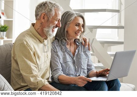 Happy Older Middle Age Family Couple Using Laptop Sit On Couch. Smiling Senior Adult Mature Man And