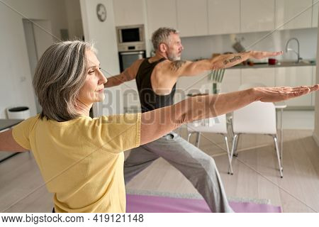 Fit Middle Aged 50s Family Couple Doing Warrior Yoga Exercise At Home. Sporty Healthy Old Mature Man