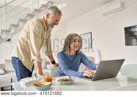 Happy Middle Aged 50s Family Couple Having Fun Using Laptop Computer Technology At Home. Smiling Sen