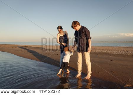 A Young Family With A Three Year Old Son Walks Barefoot Along The Wild Evening Beach.