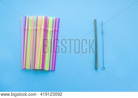 Many Plastic Drinking Straws Vs One Reusable Bamboo Drinking Straw On A Blue Background. Zero Waste
