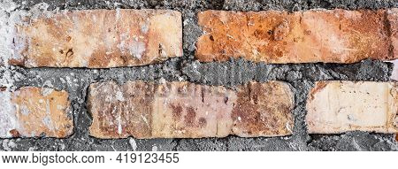 Vintage Textured Background Of Red Brick Wall. Old Brick Wall With Cracks And Scratches. Horizontal