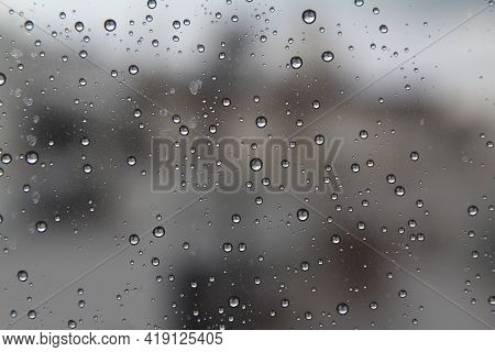 Rain Drops On The Glass In The Spring Afternoon. Close Up Of A Window With Rain Drops Falling Down.t