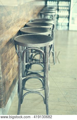 Wood alcoholic  bar chairs and bar counter. Vintage retro old film effect.