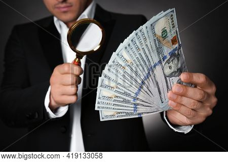 Expert Authenticating 100 Dollar Banknotes With Magnifying Glass Against Dark Background, Closeup. F