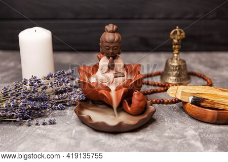 Buddha Statue With Candle Burning And Incense Smoke. Buddha Figurine And Smoky Incense With Candle,
