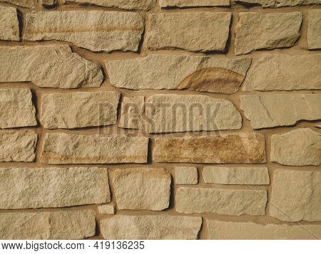 Closeup View Of Sand Stone Rock Wall With Colored Grout Matching With Shadows And Details