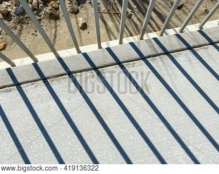 Sunlight Through A While Metal Fence With Shadows Casting On Concrete Sidewalk Diagonal View