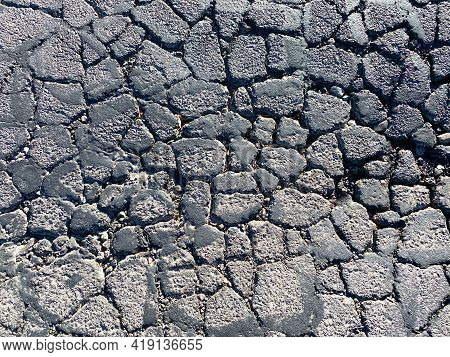 Closeup Overhead View Of Cracked Asphalt Road Street Damaged In Sunlight Decay Drought