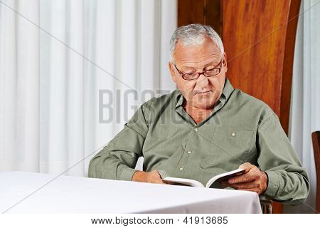 Senior man in rest home reading a book with reading glasses