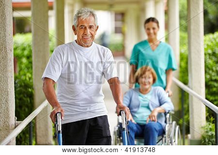 Happy senior people in nursing home with walker and wheelchair