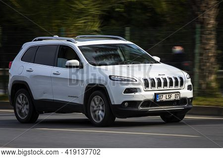 Alanya, Turkey - April 12 2021:    White  Jeep Grand Cherokee    Is Driving Fast On The Street On A