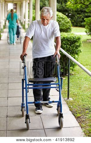 Senior man on a walk with walker in the garden of a hospital
